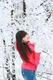 A girl stands near the snow-covered trees look upwards. A young girl stands near the snow-covered trees look upwards Royalty Free Stock Photo