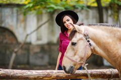 The girl stands next to the horse and smiles. Outside. Stock Photo
