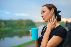 A girl stands outside with cup of tea Royalty Free Stock Photography