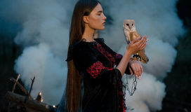 Girl stands with owl on her hand in forest against smoke backgro Royalty Free Stock Image