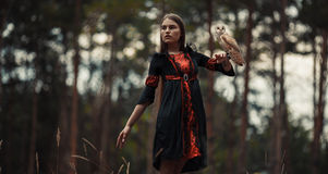 Girl stands with owl on her hand in forest. Stock Photos