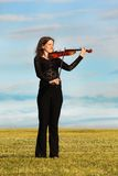 Girl stands and plays violin against sky stock photos