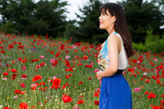 Girl stands in poppy field stock photography