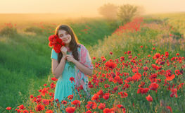 Girl stands in poppy field Stock Photo
