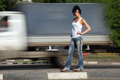 Girl stands on road among cars Royalty Free Stock Images