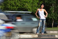 Girl stands on road among cars Royalty Free Stock Image