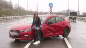 A woman was in an accident on the road in the rain, she is injured and scared. The girl stands on the road under heavy rain after a car accident, she feels fear stock video