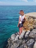 Girl stands on rocks, rocks and looks at the Caribbean Sea. The girl stands on rocks, rocks and looks at the Caribbean sea. A rocky shore is washed by blue water Stock Photo