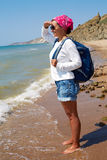 Girl stands on the sandy shore with a backpack and looking at th Stock Photo