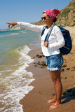 Girl stands on the sandy shore with a backpack and looking at th Stock Image