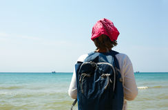Girl stands on the sandy shore with a backpack and looking at th Stock Photography