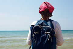 Girl stands on the sandy shore with a backpack and looking at th Royalty Free Stock Photos