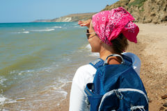 Girl stands on the sandy shore with a backpack and looking at th Royalty Free Stock Photo