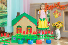 A girl stands at the scenery house on matinee in kindergarten Stock Photos
