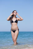 Girl stands in seawater with arms raised Royalty Free Stock Photos