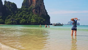 Girl Stands in Shallow Sea Foamy Waves Photos. KRABI/THAILAND - DECEMBER 04 2014: Backside view girl stands in shallow azure sea foamy waves photos people stock video