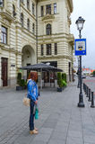 Girl stands at taxi stop near Lithuanian National Philharmonic in Old Town, Vilnius, Lithuania Stock Images