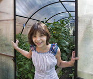Girl stands on the threshold of greenhouses. And smiles Royalty Free Stock Photography