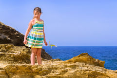Girl stands on top of cliff. Bali, Crete Royalty Free Stock Photography