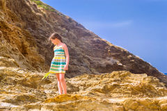 Girl stands on top of cliff. Bali, Crete Stock Photo