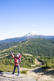 A girl stands on top of a mountain. Royalty Free Stock Photo