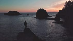 Girl stands on top of sea stack of Oregon coast watching twilight. This is a footage of a girl stands on top of sea stack of Oregon coast watching beautiful stock footage