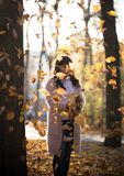 The girl stands under the autumn falling leaves in the park. Autumn. The girl stands under the autumn falling leaves in the park stock photography