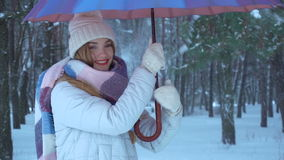 Girl stands under the umbrella and twists it, and pour around snow stock video footage