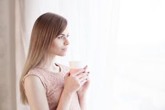 Girl stands at the window with a mug Royalty Free Stock Photography