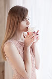 Girl stands at the window with a mug Stock Images