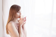 Girl stands at the window with a mug Royalty Free Stock Image