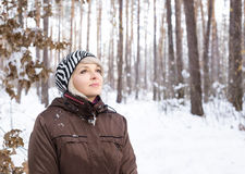 Girl stands in a winter forest and looks up. Royalty Free Stock Photography