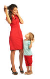 Girl stands with woman in red dress stock images