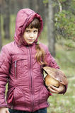 Girl stands in the woods with a large mushroom . Royalty Free Stock Photo