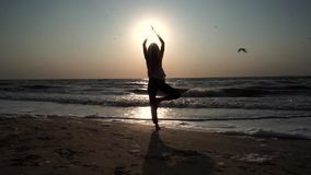 Girl stands in a yoga pose, opposite the sun at sunset, on the beach, on the sea stock video