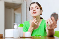 Girl  stares on her neck. Girl in green stares on her neck in mirror at home Stock Photos