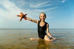 Girl with starfish. Stock Image