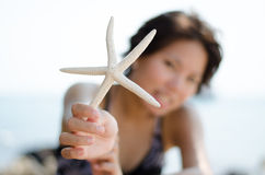 Girl with starfish at the beach Royalty Free Stock Image
