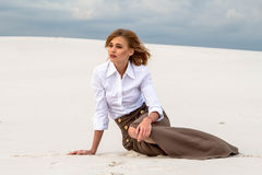 The girl is staring into the distance, sitting in the middle of the desert Royalty Free Stock Photos