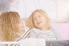 Girl staring at her mom. Little girl staring at her mom and smiling Stock Photos