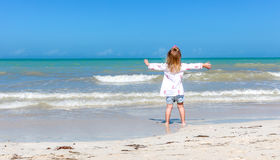 Girl staring  at the ocean. One Little girl staring at the ocean on a Yucatan beach Royalty Free Stock Photo