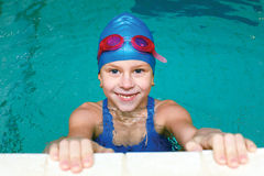 Girl start to swimming pool. Beautiful girl in a bathing suit, swim cap, goggles, holding on overboard in a swimming pool Royalty Free Stock Photography