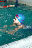 Girl start to swimming pool. Beautiful girl in a bathing suit, swim cap, goggles, holding on overboard in a swimming pool Stock Photos