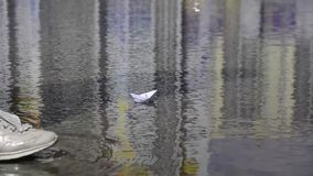 Girl start up paper boat in a puddle.  stock video footage