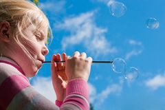 Girl starting up soap bubbles Stock Photography