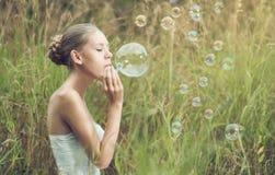 Girl starts soap bubbles Royalty Free Stock Photo