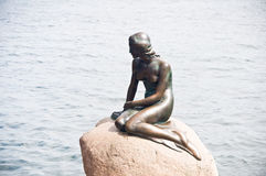 Girl statue sitting on rock Royalty Free Stock Images