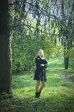 Girl stayning under the dark mysterious tree Royalty Free Stock Photos
