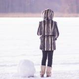 Girl stays near dead snowman royalty free stock photo