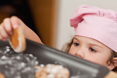 Girl stealing a cookie Stock Photos